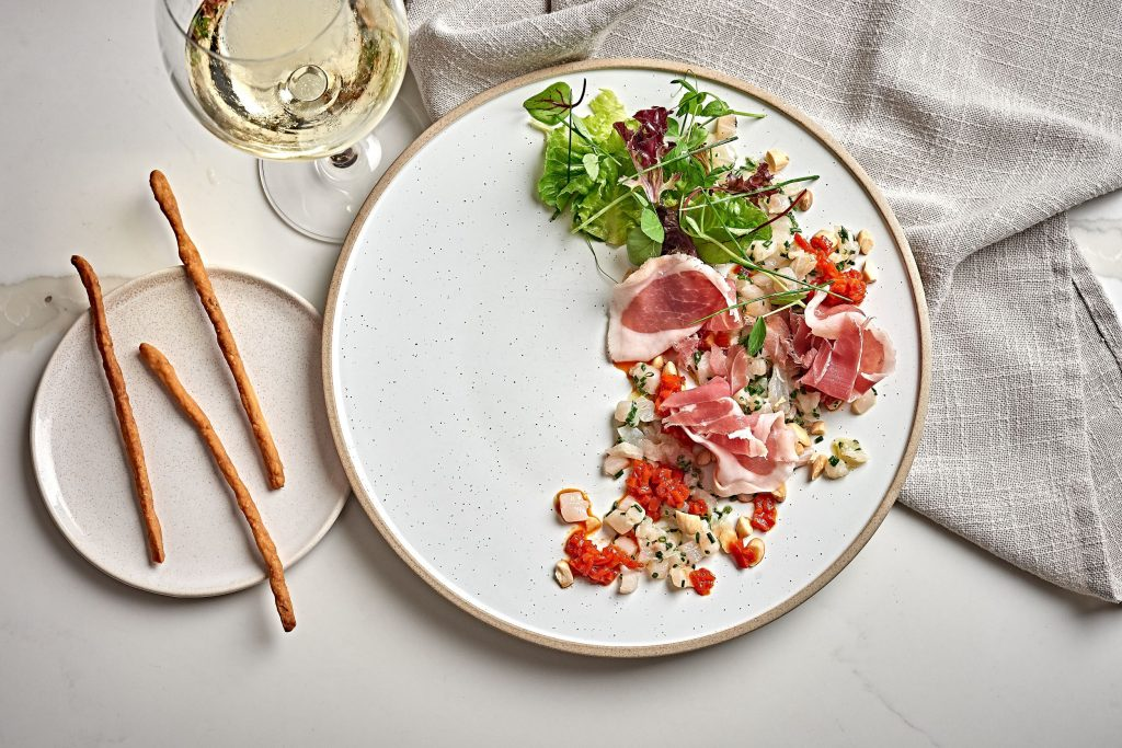 A white plate featuring cobia crudo with peppers, almonds and prosciutto