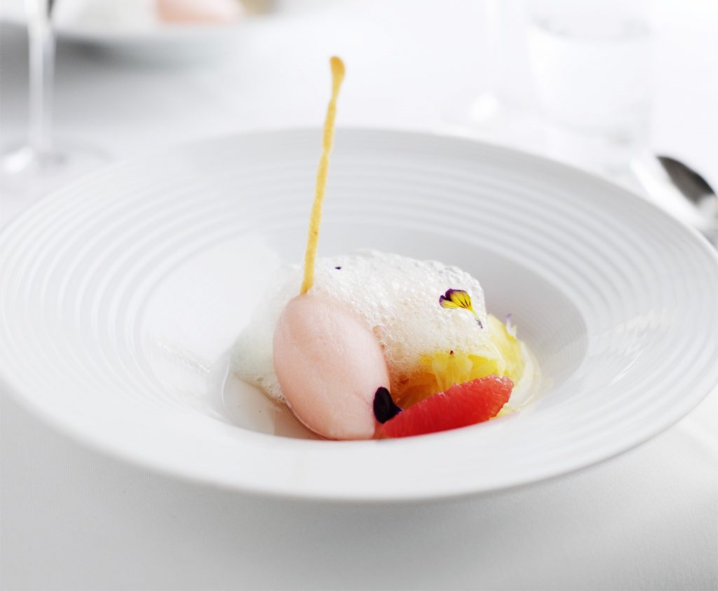 A white bowl filled with pink grapefruit sorbet