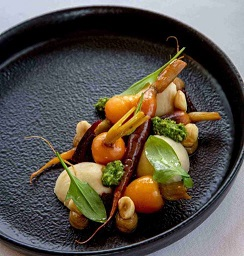 A black plate featuring heirloom baby carrot salad