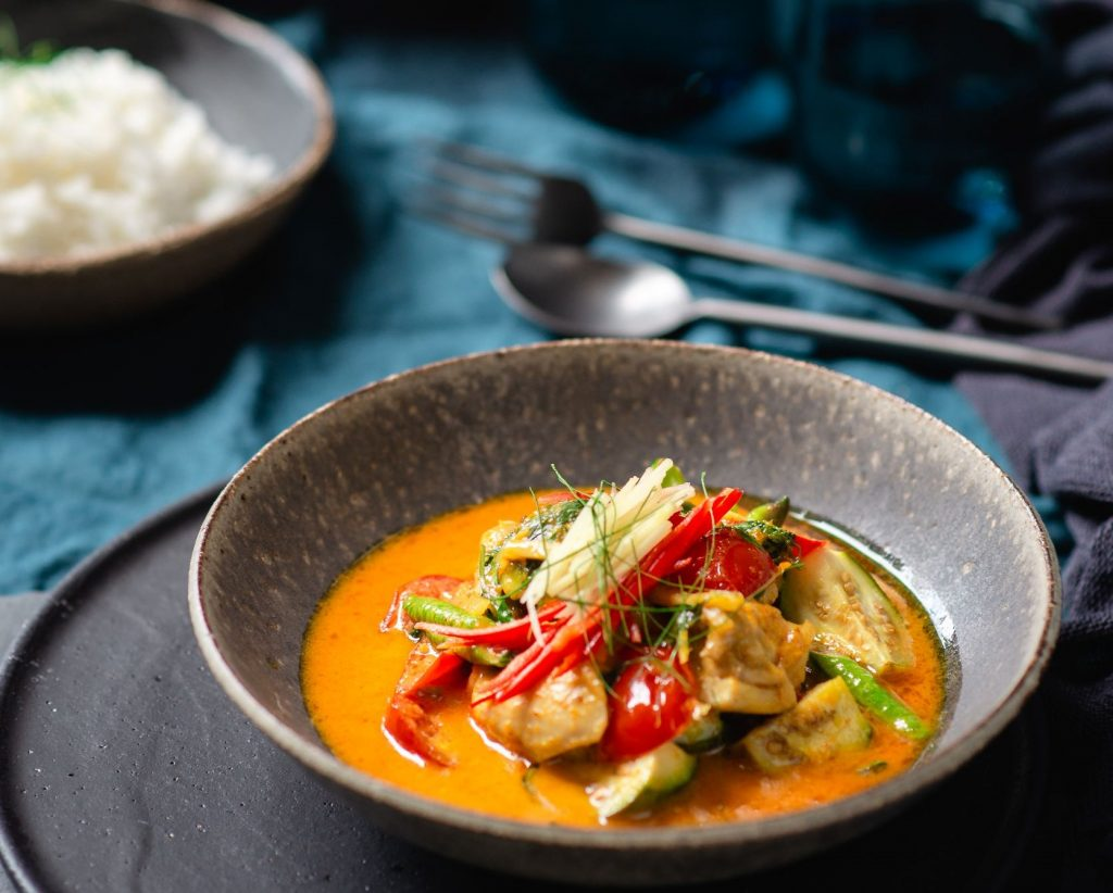 A grey bowl filled with yellow chicken curry