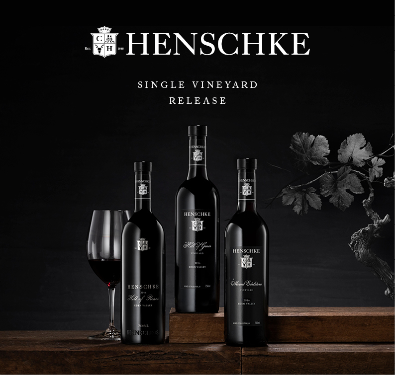 Three bottles of Henschke single vineyard wine and a half filled glass of Hill of Roses